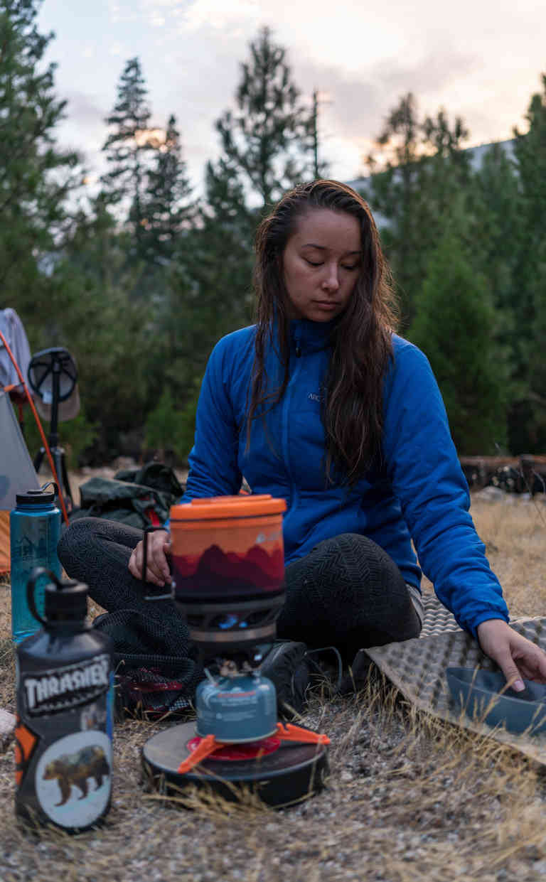 girl sitting with camping stove