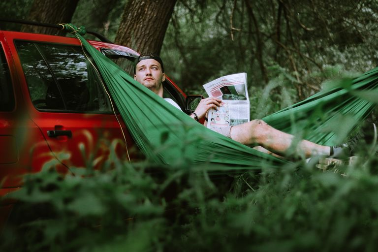 man lying on a hammock tied to a pickup