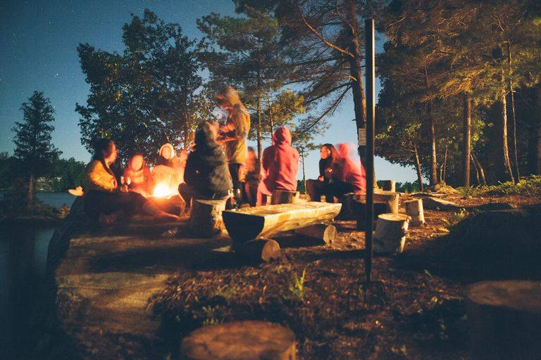 group of campers gathered around a bonfire
