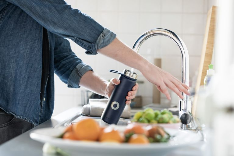 person filling a steel bottle with tap water