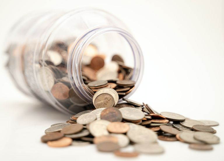 a tipped jar with coins spilling out