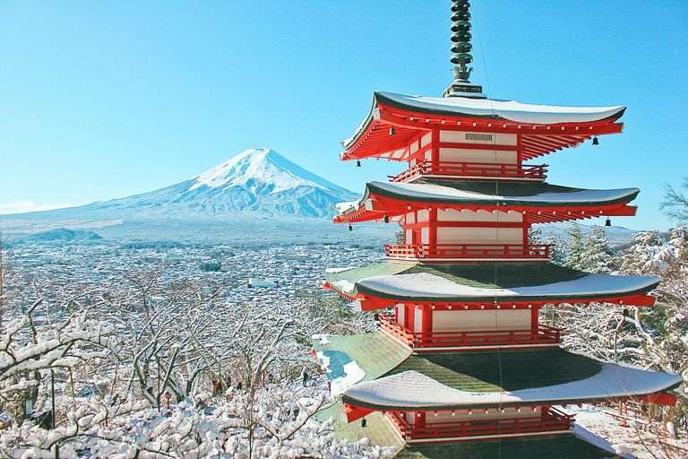 a view of a pagoda and mt fuji during winter