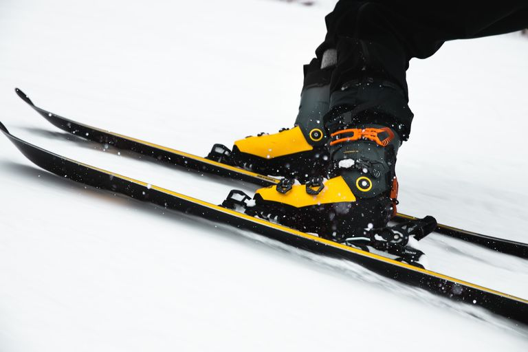 yellow ski boots attached to skis
