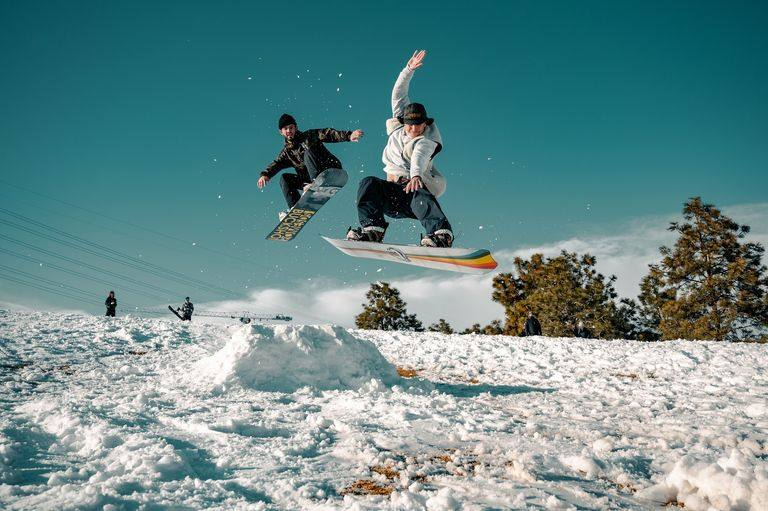 snowboarders jumping over an obstacle