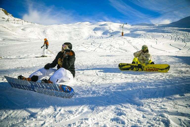 snowboarders resting on a slope